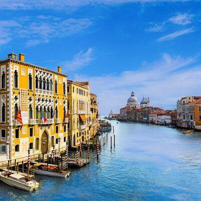 Der Canal Grande (Venedig) fließt durch die mitte des Bildes. Links sind gelbe Gebäude am Wasser. In der Ferne kann eine art Ratshaus gesehn werden.