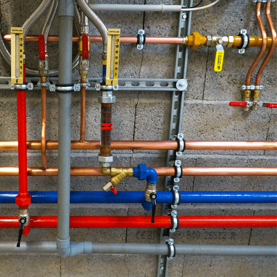 Viele Rohre aus verschiedenen Materialien an einer Steinwand