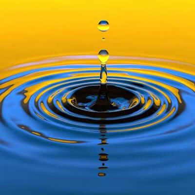 Ein Tropfen der auf stilles Wasser fällt und kleine wellen auf der Oberfläche auslöst